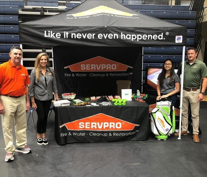 4 people around a SERVPRO tent